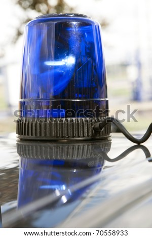 Blue  magnetic emergency flashing light on top of an unmarked police car