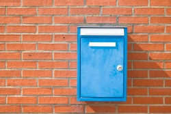 blue mailbox on a red brick wall