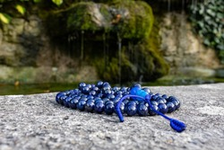 Blue mala beads (lapislazuli) on stone with flowing water and green leaves in the background. Mindfulness and meditation accessory.