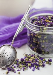 Blue mallow flowers tea in glass jar with vintage strainer infuser on light background with purple cloth and ceramic teapot