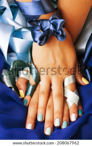 blue manicure with ribbon close up as a gift