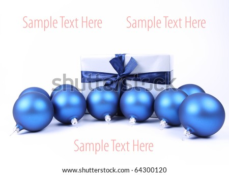 Blue matt christmas balls and a gift in red wrapping on white background, with space for your text