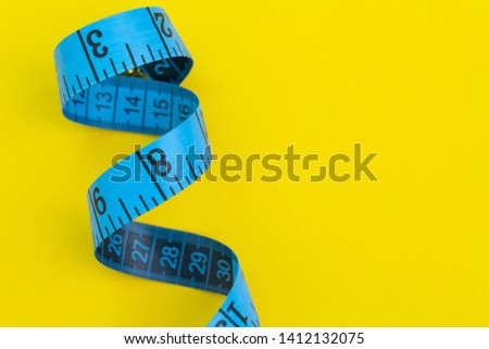 Blue measuring tape on solid yellow background with copy space using as measurement, health fitness, nutrition, exercise or diet concept.