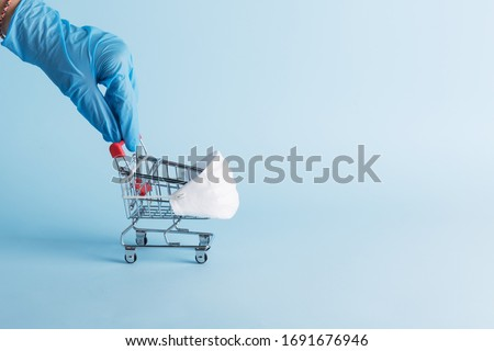 Blue medical gloved hand pull a grocery trolley cart in protective mask. Hygiene in store. Concept of shortages of essential commodities in Coronavirus and online shopping. Pandemic COVID-19