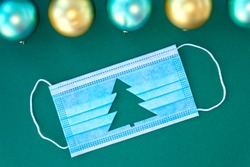 Blue medical protective mask with cut-out silhouette of Christmas tree on green background. With Christmas balls near mask. Christmas and Happy New Year concept, coronavirus concept. Soft focus