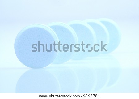 Blue medicine pills on light blue background
