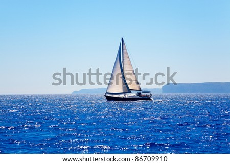 Blue Mediterranean sailboat sailing in perfect ocean at San Antonio cape