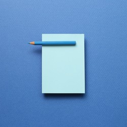 Blue memo note pad and blue colored pencil on blue background