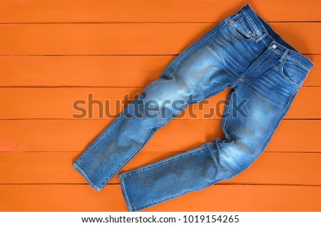 Blue mens jeans denim pants on orange background. Contrast saturated color. Fashion clothing concept. View from above #1019154265