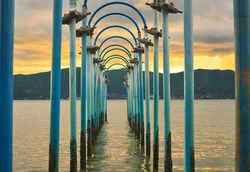 blue metal arch in the sea for seascape at sunset skyline and mountain in tunnel concept background