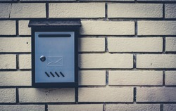 Blue metal mailbox mounted on the brick wall, mailbox has a letter engraving on it
