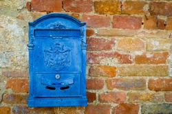 Blue metal mailbox on a brick wall in Monteriggioni, Tuscany, Italy.