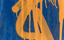 Blue metal panel with yellow paint close up