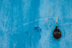 Blue metal wall and old rusty padlock