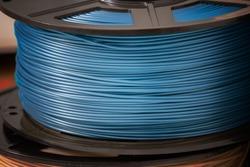 Blue metallic glossy PLA plastic filament for 3D printer.
