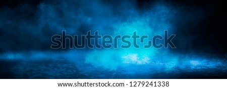 Blue misty dark background. Dark street with smoke, fog, blue spotlights, neon. Dark abstract empty background.