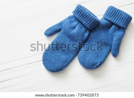 blue mittens on white wooden background #739402873