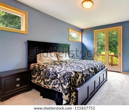 Blue modern bedroom with balcony door and beige carpet.