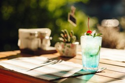 Blue Mojito cocktail with a cherry, ice and mint. A glass with a blue lagoon alcohol cocktail on the table in the restaurant. Selective focus.