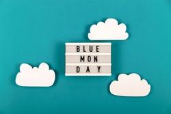 Blue Monday inscription among paper clouds on a blue background. Depressive mood concept