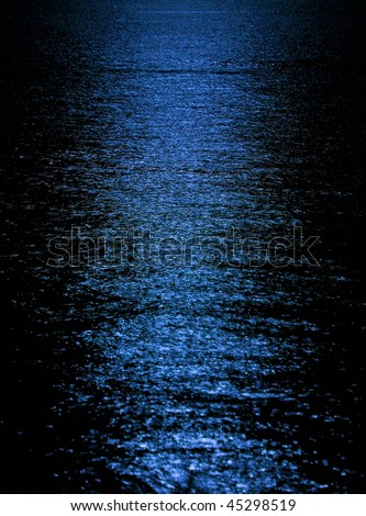 Blue moon light reflection on calm but rippled water