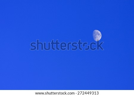 Blue moon of the Nordic bright sky. Half moon against a bright blue afternoon sky.