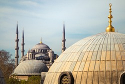 Blue Mosque or Sultanahmet Camii Mosque in Istanbul. View of ancient Turkish temple with minarets through the window of the Hagia Sophia with church dome, golden spire and arabic symbol on the roof.