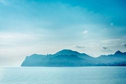 Blue mountains and blue sea. Silhouette of the mountain Karadag volcano. Black Sea Crimea.