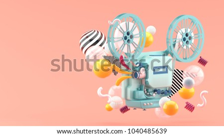 Stock Photo Blue movie projector amid colorful balls on pink background.-3d render.
