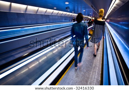 Blue moving escalator with people in Barcelona's subway