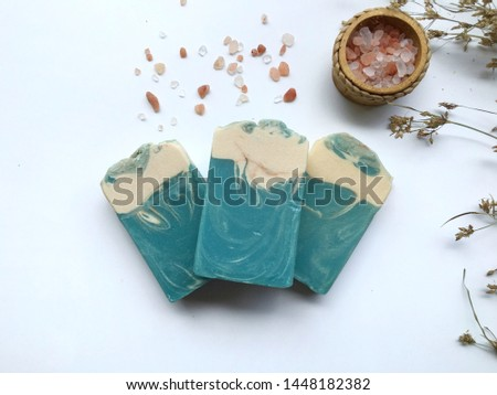 Blue natural oil soap with himalayan pink salt on white background, cold process.