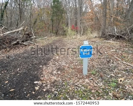 blue nature trail sign with trail or path and trees