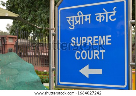 Blue NDMC board pointing towards the Supreme Court of India complex in Patel Marg, central part of Lutyen's Delhi. The Supreme court is the most revered and highest court of justice in the country Photo stock ©