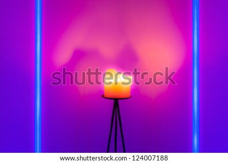 Blue neon tube lights and a burning candle with three flames