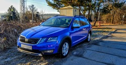 Blue new Skoda car with sunrise in winter sunny morning near railway track
