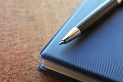 blue notebook and ball pen on an old  wooden background, close up view with copy space.
