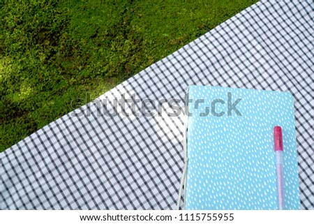 Blue notebook and pink pen on tartan black and white fabric at the public park. Feeling Relax. Write personal diary or plan schedule. Feel fresh. Beautiful background. Business, Education. Copy space. #1115755955