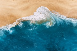 Blue ocean and clean sandy beach. Beautiful sea and wild beach with yellow sand. Blue ocean wave on a sandy beach. Top view of the tropical beach. Paradise island. Copy space