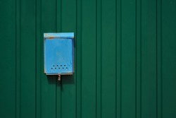 Blue old rusty mailbox on the green metal fence with a copy space