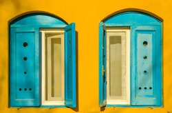 Blue old style wooden windows, symmetry in open doors, yellow house wall background in small town, minimal style of simplicity, trendy look, contrast bright colors, modern postcard art design concept