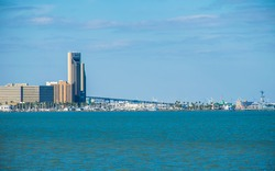Blue open water across the bay Corpus Christi Texas sunny day along the coastal bend afternoon hours as the sun begins to set on with towers and skyline cityscape and harbor marina and the battleship