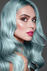 Blue or turquoise hair.  Dye for coloring. Close up portrait of fashion model with stylish make up, pink lips and brown eye shadow.