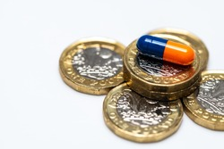 Blue & Orange drug medicine pills colored capsules closeup with pound coin on white background
