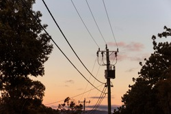 Blue & orange gradient sunset with silhouetted powerline running along roadside.