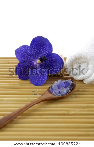Blue orchid with towel sea salt in spoon on mat