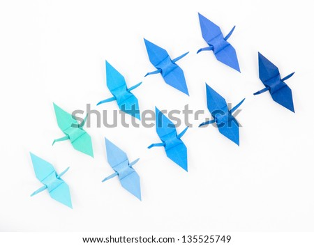 Blue origami paper cranes on a white background