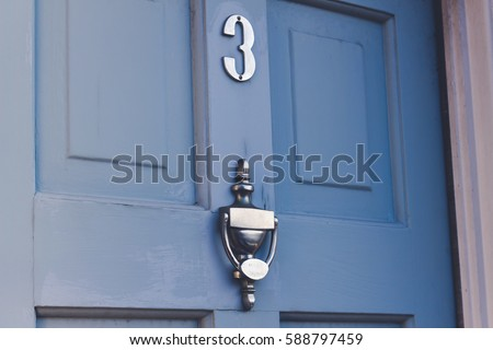 Blue outside entrance door, close up, with a metal door knocker and a number 3 house number.