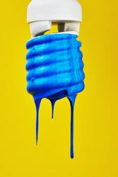 blue paint flowing down an energy saving light bulb on a yellow background close-up