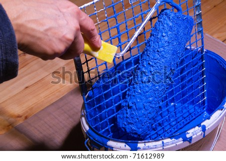 Blue paint in a bucket with painter's tools