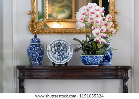 Blue paint porcelain collection with Orchid vase on a dark wooden table with golden mirror on white wall. #1151055524